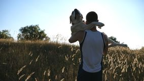 Young man carrying on hands his dog by field. Playing with labrador or golden retriever at nature. Love and friendship
