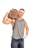 Young man carrying a heavy log over his shoulder Royalty Free Stock Images
