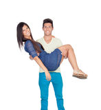 Young man carrying his girlfriend in his arms Stock Photos
