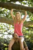 A young man carrying his girlfriend on shoulders in the woods, close-up Stock Photos