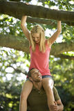 A young man carrying his girlfriend on shoulders in the woods Royalty Free Stock Images