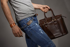 Young man carrying a leather bag. Against grey background Stock Photos