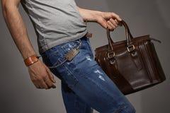 Young man carrying a leather bag Stock Photos