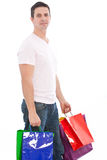 Young man carrying many shopping paper bags Stock Photo