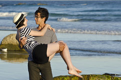 Young man carrying pretty woman at seaside Royalty Free Stock Image