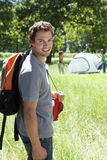 Young man carrying rucksack and sleeping bag to camp in woodland clearing, smiling, portrait, friends assembling tent Stock Image