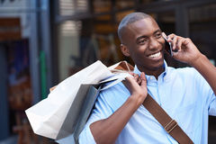 Young man carrying shopping bags talking on his cellphone outside. Stylish young African man smiling and talking on his cellphone while carrying paperbags while stock photos
