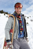 Young Man Carrying Sled In Alpine Landscape Royalty Free Stock Photography