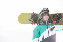 young man carrying snowboard against clear sky Stock Photography