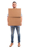 Young man carrying some boxes. Full length view of a young man carrying a couple of cardboard boxes and getting ready to ship them away stock images