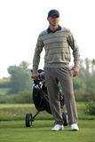 Young man carrying trolley with golf bag Stock Photo