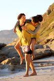 Young man carrying woman on his back at the beach Stock Photography