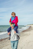 Young man is carrying woman on his shoulders on the beach Royalty Free Stock Photo