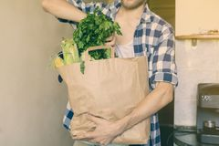 Young man in casual came home from a food store and bought some fresh grocery in a paper bag. Young man in casual came home from a food store and bought some stock photo
