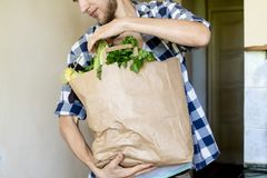 Young man in casual came home from a food store and bought some fresh grocery in a paper bag. Young man in casual came home from a food store and bought some royalty free stock images