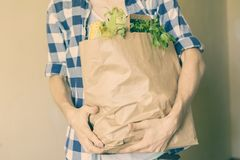 Young man in casual came home from a food store and bought some fresh grocery in a paper bag. Young man in casual came home from a food store and bought some Stock Image