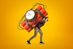 Young man in casual clothes carrying big red dynamite stick time bomb on his back on yellow background stock photos