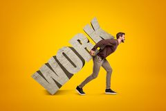 Young man in casual clothes carrying heavy WORK sign on his back on yellow background royalty free stock photography