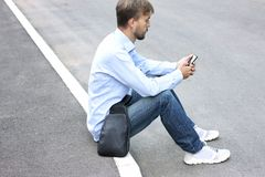Young man in casual clothes and modern leather bag sitting on th stock images