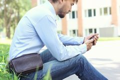 Young man in casual clothes and modern leather weist bag sitting royalty free stock image