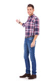 Young man in casual clothes presenting Royalty Free Stock Image