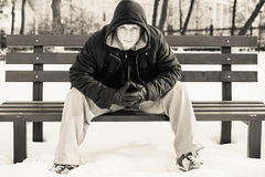Young man in casual clothes sitting on winter bench Royalty Free Stock Photo