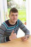 Young man in casual posing with mobile phone Royalty Free Stock Images