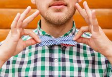 Young man in casual shirt correcting his retro bowtie Royalty Free Stock Images