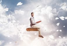 Handsome man student reading book and paper planes flying around. Young man in casual sitting on old book with one in hands Royalty Free Stock Photo