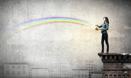 Young man in casual splashing rainbow from bucket Royalty Free Stock Photos