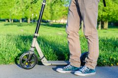 Young man in casual wear on kick scooter in park Stock Photos