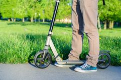 Young man in casual wear on kick scooter in park Royalty Free Stock Images