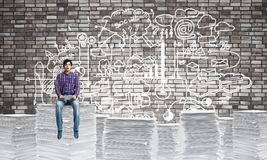 Attractive man sitting on pile of paper documents. Young man in casual wear sitting on pile of documents with business-analytical information on background Stock Photos