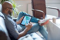 Analyst with tablet. Young man in casualwear analyzing online statistics in tablet while sitting on sofa royalty free stock photo