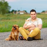 A young man with a cat and a dog are sitting on the road, the gu stock image