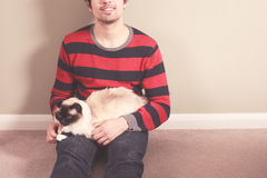 Young man and cat sitting on the floor Stock Photo