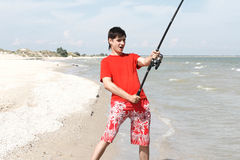 A young man catches a fish Stock Photos