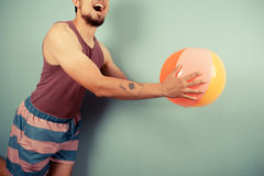 Young man catching beach ball Royalty Free Stock Photos