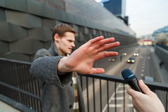 A young man is categorically against giving an interview to a journalist on the street. Royalty Free Stock Photos