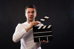 Young man of Caucasian appearance is holding a clapperboard. Portrait shot in studio on a black background with smoke and red and stock photo