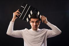 Young man of Caucasian appearance is holding a clapperboard. Portrait shot in studio on a black background with smoke and red and royalty free stock photography