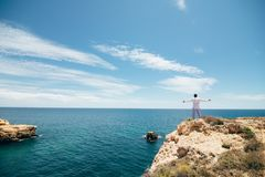 Young man celebrate victory on the edge of cliff on ocean background. Freedom concept. stock photos