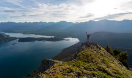 Young man celebrates reaching the peak of a mountain. Young man celebrates successfully reaching the peak of a mountain royalty free stock photography