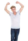 Young man celebrating with arms raised. Portrait of a young man celebrating with arms raised on isolated white background Royalty Free Stock Photo