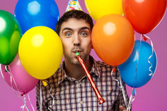Young man celebrating birthday, holding colorful baloons over purple background. Stock Photos