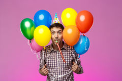 Young man celebrating birthday, holding colorful baloons over purple background. Royalty Free Stock Photo