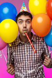 Young man celebrating birthday, holding colorful baloons over purple background. Royalty Free Stock Photos