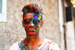 Young man celebrating of Holi festival with colored powder on face, Yerawada royalty free stock image