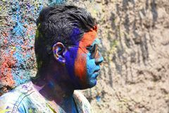 Young man celebrating of Holi festival with colored powder on face, Yerawada royalty free stock photos