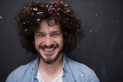 Man blowing confetti in the air. Young man celebrating new year and chrismas party while blowing confetti decorations to camera Royalty Free Stock Image
